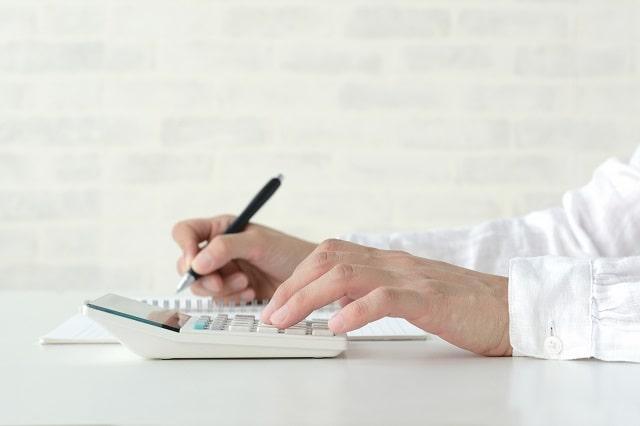 ペンを持つ手と電卓