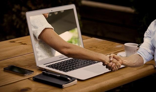 握手している手とパソコン